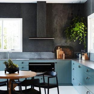 Diseño de cocina comedor en L, exótica, de tamaño medio, con fregadero bajoencimera, armarios con paneles lisos, encimera de cuarzo compacto, salpicadero verde, salpicadero de pizarra, electrodomésticos de acero inoxidable, suelo de madera pintada, suelo blanco, encimeras grises y puertas de armario azules