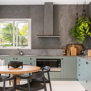 Mid-sized beach style l-shaped eat-in kitchen in Other with green cabinets, grey splashback, white floor, brown benchtop, an undermount sink and stainless steel appliances.
