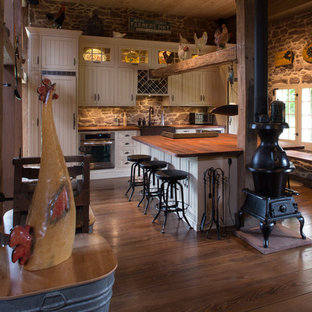 Farmhouse eat-in kitchen designs - Example of a cottage single-wall dark wood floor eat-in kitchen design in New York with a farmhouse sink, recessed-panel cabinets, white cabinets, paneled appliances, wood countertops, gray backsplash and stone tile backsplash