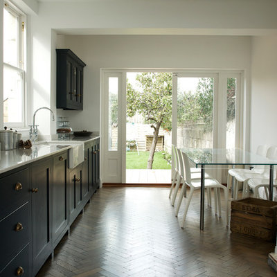 Example of a trendy dark wood floor eat-in kitchen design in Other with a farmhouse sink, shaker cabinets and blue cabinets