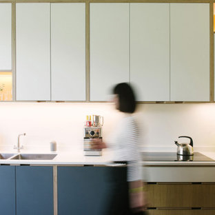 Photo of a scandi l-shaped kitchen in Other with a double-bowl sink, flat-panel cabinets, white cabinets and white worktops.