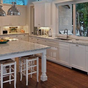 Geräumige Tropische Wohnküche in U-Form mit gelben Schränken, Küchenrückwand in Grün, braunem Holzboden und Kücheninsel in Houston