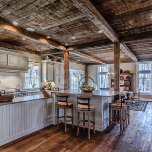 Design ideas for a large rustic l-shaped open plan kitchen in New York with raised-panel cabinets, white cabinets, granite worktops, white splashback, ceramic splashback, stainless steel appliances, dark hardwood flooring and an island.