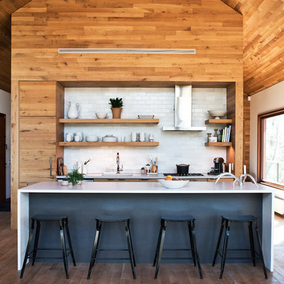 Mid-sized trendy galley medium tone wood floor and brown floor kitchen photo in New York with an undermount sink, flat-panel cabinets, medium tone wood cabinets, white backsplash, subway tile backsplash, paneled appliances, an island, white countertops and solid surface countertops
