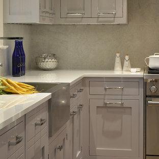 Geräumige Klassische Wohnküche in U-Form mit Landhausspüle, Schrankfronten im Shaker-Stil, grauen Schränken, Glas-Arbeitsplatte, Küchenrückwand in Grau, Kalk-Rückwand, Elektrogeräten mit Frontblende, braunem Holzboden, Kücheninsel und braunem Boden in New York