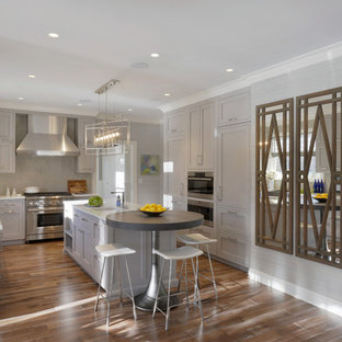 Photo of an expansive classic u-shaped kitchen/diner in New York with a belfast sink, shaker cabinets, grey cabinets, glass worktops, grey splashback, limestone splashback, integrated appliances, medium hardwood flooring, an island and brown floors.
