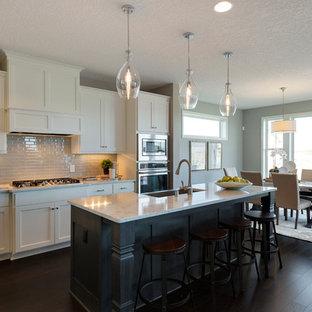 Exemple d'une cuisine romantique avec un évier posé, des portes de placard blanches, un plan de travail en quartz, une crédence blanche, une crédence en carreau de céramique, un électroménager en acier inoxydable, un sol en bois foncé et un îlot central.