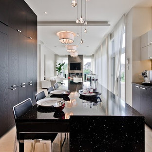 Contemporary eat-in kitchen photos - Trendy eat-in kitchen photo in Montreal with flat-panel cabinets, black cabinets, beige backsplash and black countertops