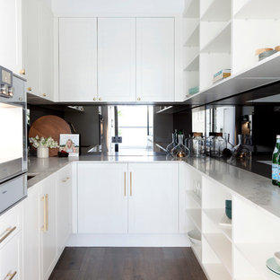 This is an example of a large classic galley kitchen in Melbourne with a single-bowl sink, shaker cabinets, yellow cabinets, engineered stone countertops, yellow splashback, stone slab splashback, stainless steel appliances, medium hardwood flooring and an island.