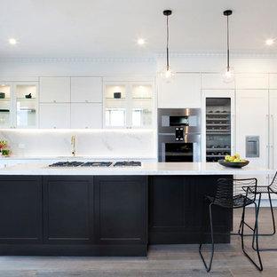 メルボルンの大きいトランジショナルスタイルのおしゃれなキッチン (シングルシンク、シェーカースタイル扉のキャビネット、黄色いキャビネット、クオーツストーンカウンター、黄色いキッチンパネル、石スラブのキッチンパネル、シルバーの調理設備の、無垢フローリング) の写真