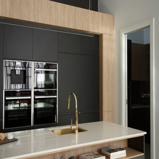 Photo of a large modern galley kitchen pantry in Melbourne with a single-bowl sink, black cabinets, engineered stone countertops, metallic splashback, mirror splashback, black appliances and an island.