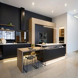 Inspiration för ett stort funkis kök, med en enkel diskho, svarta skåp, bänkskiva i kvarts, stänkskydd med metallisk yta, spegel som stänkskydd, svarta vitvaror och en köksö