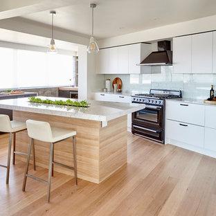 メルボルンの広いコンテンポラリースタイルのおしゃれなアイランドキッチン (フラットパネル扉のキャビネット、大理石カウンター、淡色無垢フローリング、ドロップインシンク、白いキャビネット、白いキッチンパネル、黒い調理設備) の写真