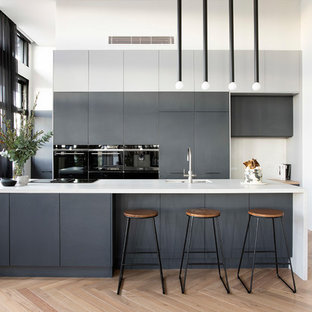 This is an example of a contemporary galley kitchen in Sydney with an undermount sink, flat-panel cabinets, grey cabinets, black appliances, medium hardwood floors, with island, brown floor and white benchtop.