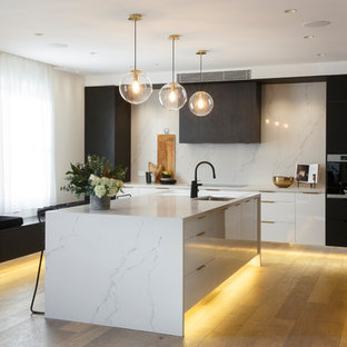 Photo of a contemporary l-shaped kitchen in Sydney with an undermount sink, flat-panel cabinets, white cabinets, white splashback, stone slab splashback, medium hardwood floors, with island, brown floor and white benchtop.