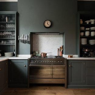 На фото: кухня в стиле современная классика с раковиной в стиле кантри, открытыми фасадами, серыми фасадами, белым фартуком, техникой из нержавеющей стали и паркетным полом среднего тона с