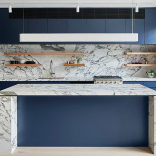 Photo of a mid-sized modern l-shaped eat-in kitchen in Melbourne with an undermount sink, flat-panel cabinets, blue cabinets, marble benchtops, white splashback, marble splashback, black appliances, light hardwood floors, with island, beige floor and white benchtop.