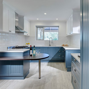Inspiration for a small timeless u-shaped beige floor enclosed kitchen remodel in Adelaide with an undermount sink, recessed-panel cabinets, blue cabinets, white backsplash, subway tile backsplash, stainless steel appliances and a peninsula