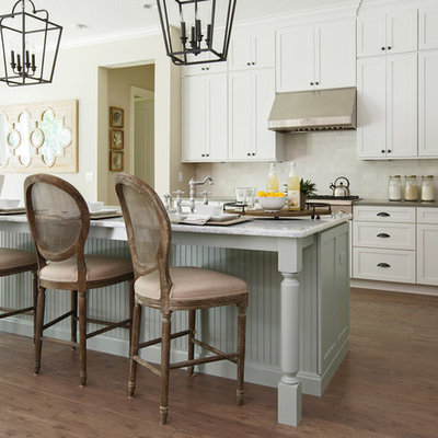 Kitchen - large traditional galley dark wood floor and brown floor kitchen idea in Jacksonville with shaker cabinets, white cabinets, white backsplash, stainless steel appliances, an island, an undermount sink, marble countertops and porcelain backsplash