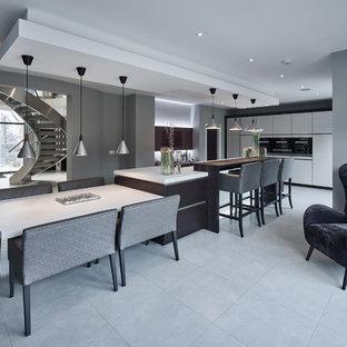 Ejemplo de cocina contemporánea, extra grande, abierta, con fregadero integrado, armarios con paneles lisos, puertas de armario grises, encimera de acrílico, electrodomésticos de acero inoxidable, suelo de baldosas de porcelana y una isla