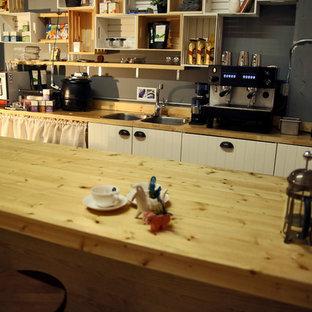 マイアミの巨大なサンタフェスタイルのおしゃれなキッチン (ダブルシンク、フラットパネル扉のキャビネット、白いキャビネット、木材カウンター、シルバーの調理設備の、コンクリートの床) の写真