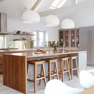 Ejemplo de cocina comedor en L, contemporánea, grande, con puertas de armario grises, encimera de madera, electrodomésticos con paneles, suelo de madera clara, una isla, armarios abiertos, salpicadero de vidrio y suelo beige