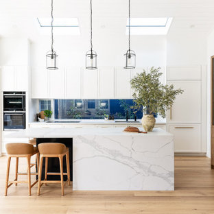 Inspiration for a large beach style galley kitchen in Sydney with shaker cabinets, white cabinets, marble benchtops, with island, white benchtop, vaulted, timber, window splashback, panelled appliances, medium hardwood floors and brown floor.