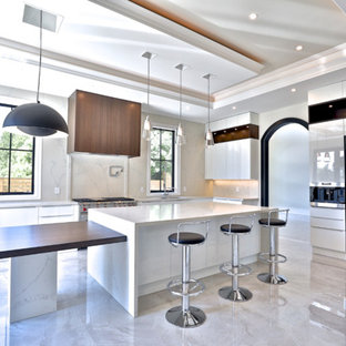 Mid-sized modern u-shaped separate kitchen in Toronto with a double-bowl sink, flat-panel cabinets, white cabinets, limestone benchtops, beige splashback, limestone splashback, stainless steel appliances, laminate floors, multiple islands, beige floor and white benchtop.