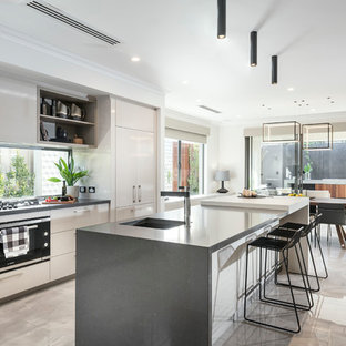 This is an example of a contemporary galley eat-in kitchen in Perth with an undermount sink, flat-panel cabinets, beige cabinets, window splashback, black appliances, with island and beige floor.