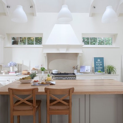 Kitchen - traditional kitchen idea in Dublin with recessed-panel cabinets, white cabinets and wood countertops