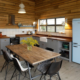This is an example of a rural l-shaped kitchen/diner in London with a belfast sink, shaker cabinets, grey cabinets, wood worktops, white splashback, no island and grey floors.