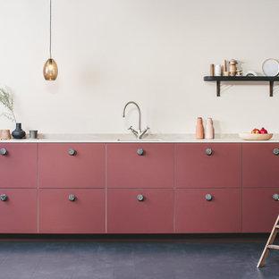他の地域の小さいコンテンポラリースタイルのおしゃれなキッチン (ドロップインシンク、フラットパネル扉のキャビネット、赤いキャビネット、人工大理石カウンター、ベージュキッチンパネル、石スラブのキッチンパネル、パネルと同色の調理設備、塗装フローリング、アイランドなし、黒い床、ベージュのキッチンカウンター) の写真