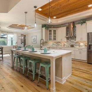 Idéer för ett maritimt vit kök, med en undermonterad diskho, skåp i shakerstil, vita skåp, flerfärgad stänkskydd, stänkskydd i stickkakel, rostfria vitvaror, ljust trägolv och en köksö