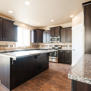 Example of an u-shaped open concept kitchen design in Salt Lake City with an undermount sink, shaker cabinets, dark wood cabinets, granite countertops, multicolored backsplash, mosaic tile backsplash and stainless steel appliances