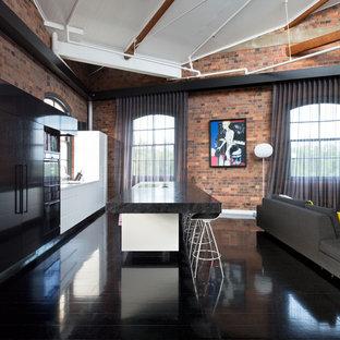 Foto di una cucina ad ambiente unico industriale di medie dimensioni con parquet scuro, isola, ante lisce, ante bianche, pavimento nero, lavello sottopiano, top in marmo e elettrodomestici neri
