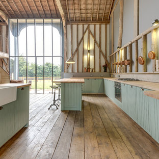 This is an example of an expansive country galley open plan kitchen in Other with a farmhouse sink, green cabinets, light hardwood floors and with island.