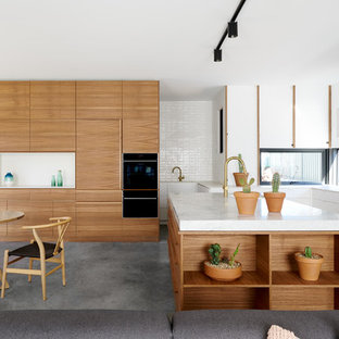 Design ideas for a contemporary l-shaped open plan kitchen in Canberra - Queanbeyan with flat-panel cabinets, white cabinets, window splashback, concrete floors, with island, grey floor and white benchtop.