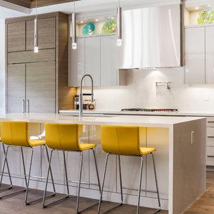 Cette photo montre une cuisine tendance avec un évier encastré, un placard à porte plane, des portes de placard grises, une crédence blanche, un électroménager encastrable, un sol en bois brun, un îlot central et un plan de travail blanc.