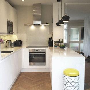 Kleine Skandinavische Wohnküche in U-Form mit flächenbündigen Schrankfronten, weißen Schränken, Arbeitsplatte aus Terrazzo, Kücheninsel und weißer Arbeitsplatte in London