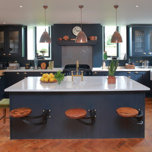 This is an example of a medium sized traditional u-shaped kitchen in Other with a belfast sink, composite countertops, medium hardwood flooring, an island, blue cabinets, ceramic splashback, glass-front cabinets, grey splashback, black appliances and orange floors.