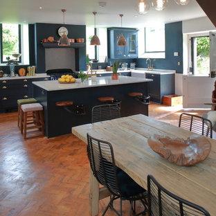 他の地域の広いヴィクトリアン調のおしゃれなキッチン (エプロンフロントシンク、シェーカースタイル扉のキャビネット、人工大理石カウンター、パネルと同色の調理設備、無垢フローリング、茶色い床) の写真