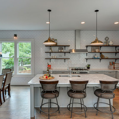 Example of a cottage l-shaped dark wood floor and brown floor eat-in kitchen design in Atlanta with an undermount sink, shaker cabinets, gray cabinets, white backsplash, subway tile backsplash, stainless steel appliances and an island