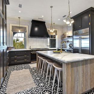 チャールストンの中サイズのカントリー風おしゃれなキッチン (エプロンフロントシンク、落し込みパネル扉のキャビネット、黒いキャビネット、白いキッチンパネル、シルバーの調理設備の、マルチカラーの床、白いキッチンカウンター、大理石カウンター、サブウェイタイルのキッチンパネル、セメントタイルの床) の写真
