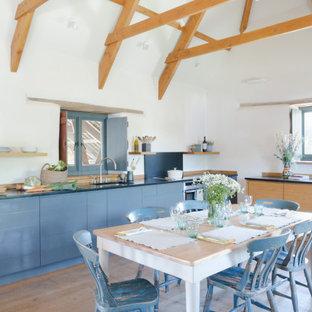 Exempel på ett stort lantligt svart svart kök, med släta luckor, granitbänkskiva, svart stänkskydd, rostfria vitvaror, mellanmörkt trägolv, brunt golv, en undermonterad diskho och blå skåp