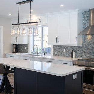 他の地域の中サイズのシャビーシック調のおしゃれなキッチン (アンダーカウンターシンク、シェーカースタイル扉のキャビネット、白いキャビネット、クオーツストーンカウンター、マルチカラーのキッチンパネル、モザイクタイルのキッチンパネル、シルバーの調理設備、ラミネートの床、ベージュの床、白いキッチンカウンター) の写真