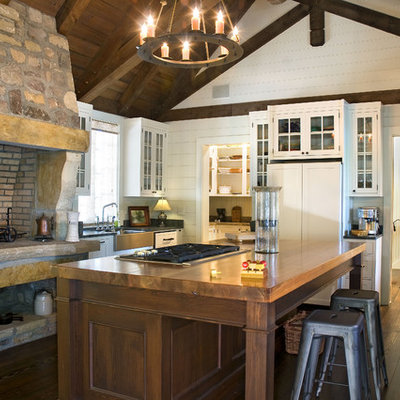Kitchen - rustic kitchen idea in Atlanta with glass-front cabinets, a farmhouse sink, white cabinets and wood countertops