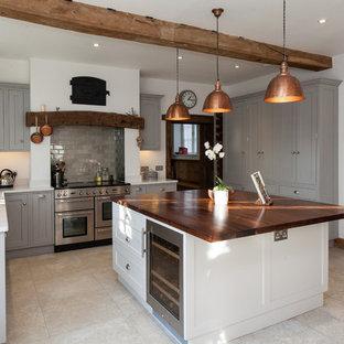 Ejemplo de cocina de estilo de casa de campo con armarios estilo shaker, puertas de armario grises, salpicadero verde, salpicadero de azulejos tipo metro, suelo de travertino y una isla