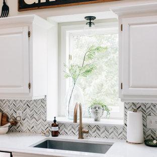 ミネアポリスの広いエクレクティックスタイルのおしゃれなキッチン (アンダーカウンターシンク、レイズドパネル扉のキャビネット、白いキャビネット、クオーツストーンカウンター、白いキッチンパネル、大理石のキッチンパネル、シルバーの調理設備、無垢フローリング、黒い床、白いキッチンカウンター) の写真