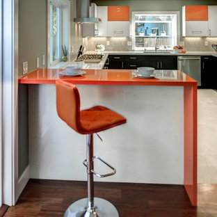 Design ideas for a mid-sized contemporary u-shaped eat-in kitchen in San Francisco with an undermount sink, flat-panel cabinets, orange cabinets, quartz benchtops, grey splashback, porcelain splashback, stainless steel appliances, porcelain floors, a peninsula and orange benchtop.