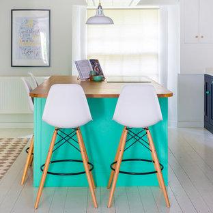他の地域の大きいエクレクティックスタイルのおしゃれなキッチン (エプロンフロントシンク、シェーカースタイル扉のキャビネット、青いキャビネット、珪岩カウンター、白いキッチンパネル、サブウェイタイルのキッチンパネル、塗装フローリング、白い床、白い調理設備) の写真
